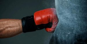 hitting the heavy bag by using boxing gloves